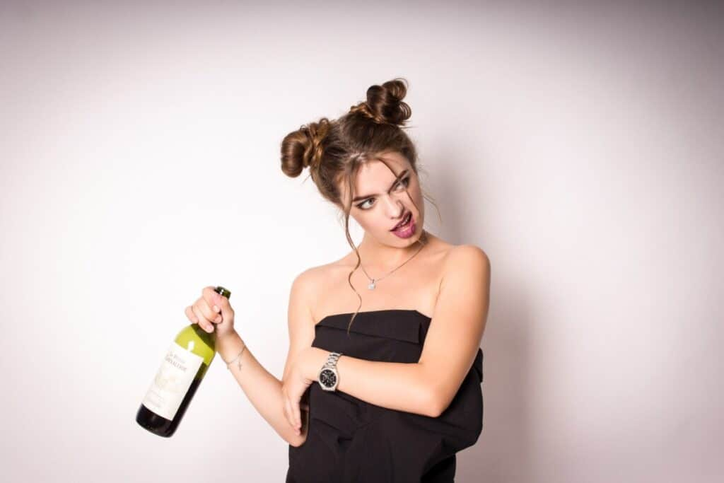 A woman who appears intoxicated is holding a bottle of wine considering whether she suffers from alcohol use disorder